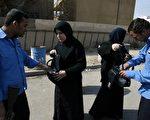伊拉克叛乱份子招募陷入绝望或一心想要报仇的妇女,充当自杀炸弹客。图为警察搜寻过往妇女皮包。(法新社)
