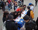 """英国民众们在街头巧遇CIPFG全球""""百万签名""""反迫害活动摊位,签下自己的姓名,为人权尽一份力量。(图/大纪元)"""