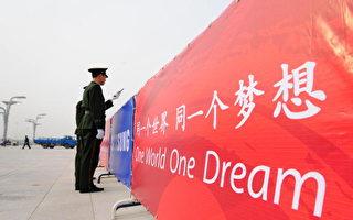 一名武警在一排巨大奥运标语前使用对讲机。(FREDERIC J. BROWN/AFP/Getty Images)