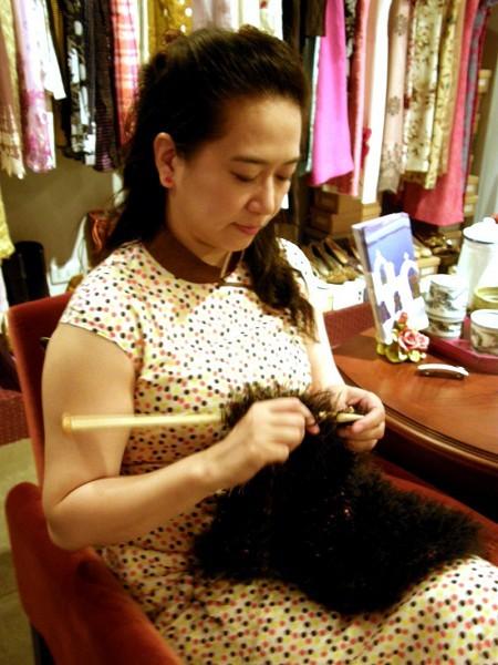 服裝設計師張雲承在工作室編織模特兒走秀時穿著的仿皮草披肩。(攝影:祝家琦/大紀元)
