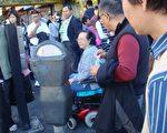 """图中轮椅妇人是长期在法拉盛街头""""蹲点""""的中共帮凶,呆在黄金商场附近辱骂法轮功学员。(大纪元图片)"""