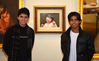 可以稱得上是大孩子的薩拉斯兄弟,里克斯(Links)在右,安隹斯(Andres)在左,在自己最喜歡的作品-獲銅獎的油畫《女孩與花瓣》前拍照留念。(攝影:文忠/大紀元)