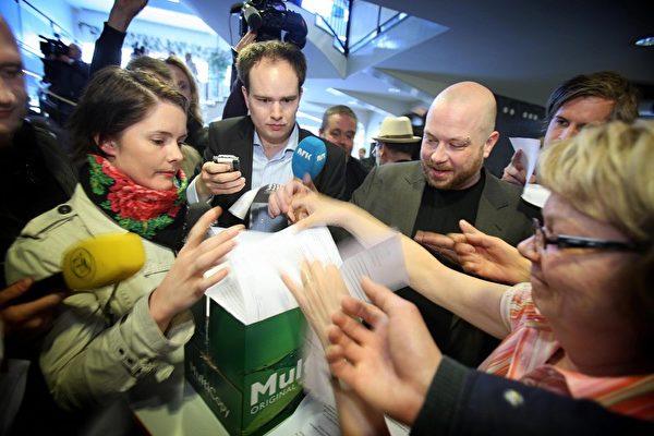 瑞典一家法院裁定檔案共享網站「海盜灣」(The Pirate Bay)的4名創辦人違反版權法罪名成立,圖為現場記者拿取法院對「海盜灣」(The Pirate Bay)的判詞。(FREDRIK PERSSON/AFP/Getty Images)
