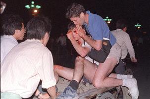 1989年6月4日,在北京天安門廣場附近,一位不知姓名的外國記者被扶出戒嚴部隊與學生衝突現場。(法新社)