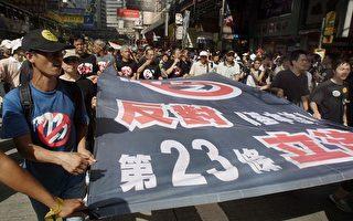 03年7月1日,50萬人上街遊行反對23條立法,圖為其中的示威者手持反23條大橫幅。(AFP)