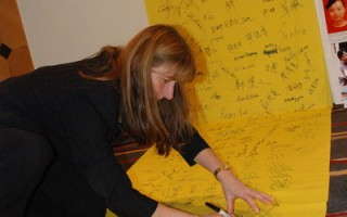 新西蘭奧克蘭市議會議員Cathy Casey博士在征簽布上簽名支持法輪功。(明慧網)