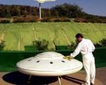 """圖片攝於2000年10月15日,在加州聖地亞哥,威廉姆(William Protor)正在擦試一個飛碟模型。該地區被Unarius科學院買下,作為未來從其它星球飛來的""""宇宙兄弟""""的降落地。(圖∕Getty Images  By: David McNew)"""