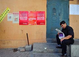 新疆烏魯木齊一名男子正在閱讀報紙,他身後的牆上張貼著政府號召「建設和諧新疆,感恩偉大祖國」的宣傳海報。(法新社/AFP)