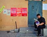 """针刺事件不但刺向王乐泉,更重要的是民众认清了中共的邪恶本质。图为新疆乌鲁木齐一名男子正在阅读报纸,他身后的墙上张贴著政府号召""""建设和谐新疆,感恩伟大祖国""""的宣传海报。(法新社/AFP)"""