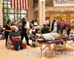 美國亞洲按摩協會麻州會長羅至良帶領的按摩隊為市民進行免費按摩。(攝影:李小旭/大紀元)