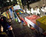 """德国纪念柏林墙倒塌20年纪念日,当人们推倒像征""""柏林墙""""的多米诺骨牌时,充满喜悦。(大纪元资料)"""