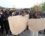 2010年1月8日,意大利羅薩諾鎮種族暴力衝突,昨天移民工人舉著抗議標語牌示威。(圖片來源:AFP)