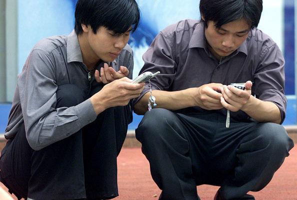 北京當局正在全國進行一項監控審查手機短訊(SMS)行動。圖為上海兩位男士正在看手機。(法新社)
