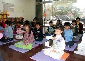 陳小妹妹(前排右一)6歲時和其他小弟子參加明慧學校,一同打坐煉功的畫面