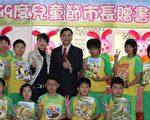 平鎮市長陳萬得和受贈兒童節禮物的學童展示新書。(攝影:徐乃義/大紀元)