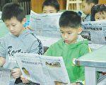 学童认真阅读大纪元时报。