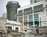 二月三日,上海一位年轻人望着一座拆毁的老房,这块地将让位给上海世博会。(AFP)