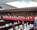 """2009年5月17日,近60名法学专家和律师参加在北京召开的法律研讨会。律师们在会上手举横幅""""强烈谴责重庆公安酷刑拷打执业律师""""。(大纪元)"""