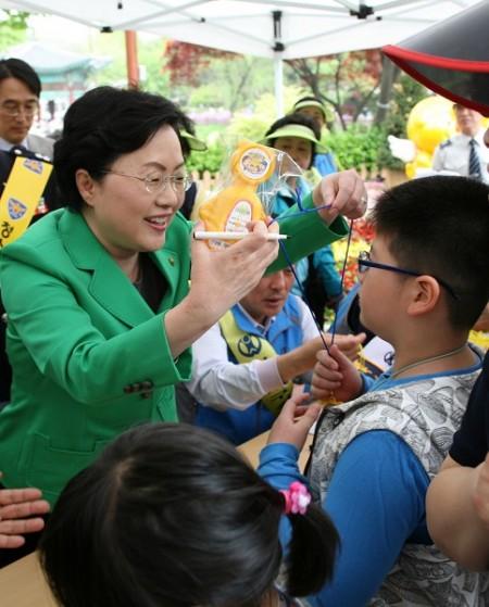為慶祝5月5日韓國兒童節,韓國女性家族部長官白姬英(音譯)當日下午來到了首爾兒童公園,拜訪了「尋找臨時失蹤兒童中心」 宣傳區,將自己簽名的吉祥物一一掛在孩子們胸前,祝福孩子們健康平安。(攝影:全宇/大紀元)