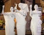 一批年青人昨晚在时代广场竖起一幅15呎高的民主女神喷画,其中三人更打扮成民主女神模样在现场站立,表示公民抗命。(摄影:潘在殊/大纪元)
