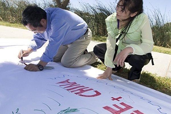 """喻日霞在看着哥哥喻东岳在""""中国人权长城""""长廊上画画。他们在6月12日周六中午,参加了在美国旧金山湾区费利蒙市风景秀丽的伊丽莎白湖畔(Elizabeth lake),为天安门勇士及家人举办的一个小型音乐、歌唱、烧烤午餐会。有30多位湾区民众参加了餐会,伴随着音乐、歌声、和烧烤,场面亲切温馨。(摄影:马有志/大纪元)"""