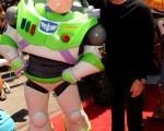 """蒂姆-艾伦(Tim Allen)与剧中的玩具巨星""""巴斯光年""""一起合影,蒂姆-艾伦在片中为""""巴斯光年""""配音。(图/Getty Images)"""
