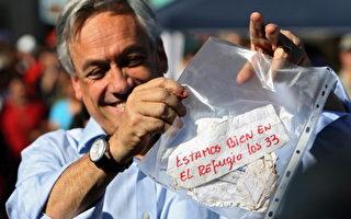 """智利总统品尼拉(Sebastian Pinera)兴奋地挥舞受困的矿工用红笔写着:""""我们33人都在避难所,全员平安。"""" 那张字条。(/Getty Images)"""