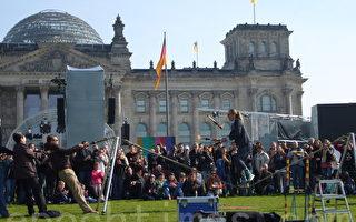 两德统一20周年纪念庆典前,在帝国大厦(背景,德国国会所在地)和德国总理府之间的草坪上,卖艺人在表演。  (摄影:文婧/大纪元)