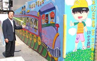 姜義芳校長展示由應屆畢業生完成的「彩繪紀念牆」。(攝影:陳建霖 / 大紀元)