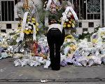 一名女士17日到上海大楼大火的现场鞠躬哀悼罹难者(图片:AFP/Getty Images)