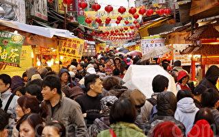 台北市迪化街年货大街即日起开卖,虽然天气冷吱吱又不时飘着小雨,民众采买年货的兴致依然不减。(摄影: 林伯东 / 大纪元)