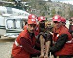 巴基斯坦官員說,巴國柯希斯坦 (Kohistan)地區偏遠村莊發生雪崩,造成30人喪生,村民用棍子和鏟子救出7人。圖為巴基斯坦志願者將受傷的倖存者轉移到一架直升機上。(SAJJAD QAYYUM/AFP/Getty Images)