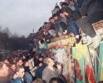 1989年12月22日,柏林墙开始被拆除,西德民众迎接翻墙前来投奔自由世界的东德民众。柏林墙的倒塌标志着东西德统一,也是共产主义势力在东欧分崩瓦解的里程碑事件。(PATRICK HERTZOG/AFP/Getty Images)