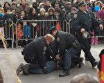 在2月12日的法拉盛新年游行庆祝活动中,一华裔男子从观众群中冲到法轮功队伍的前面,拉扯横幅并折断横杆。三个警察立即冲上去将其制服并逮捕。(大纪元)