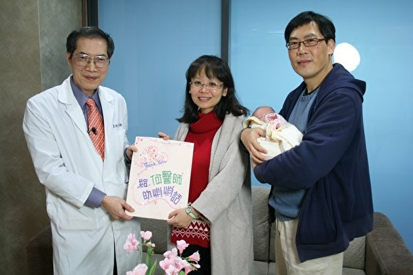 45歲的高齡產婦李小姐(中)親手製作感謝卡,在丈夫(右)的陪同下,帶著滿月的寶寶,回到嘉義基督教醫院產後護理之家向何宗錦醫師(左)致謝。(翻攝: 李擷瓔 / 大紀元)