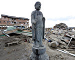 日本发生大地震并经历大海啸后,在被海啸摧毁的沿海村落中,人们发现有座佛像没有倒。 (Getty image)