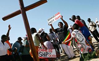 """中共商务部副部长傅自应日前在国新办新闻发布会上称,中共对非洲援助第一位的因素为""""友谊""""。图为,2008年4月19日,一基督教协会成员抗议中共向辛巴威运送武器。(RAJESH JANTILAL/AFP/Getty Images)"""
