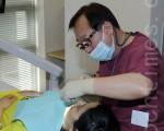 """5月22日,韩国""""SAM福利财团""""帮助30名在韩移民进行牙科诊疗,图为SAM牙科医院李健柱院长正在为患者做牙科诊疗。(摄影:全宇/大纪元)"""