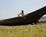 5月27日,水位则持续历史同期最低。图为当地渔民冯家棋正在草地上维护自己的渔船。(大纪元资料室)