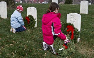 两个孩子在阿灵顿公墓的墓碑前悼念阵亡的亲人。(图片来源:NICHOLAS KAMM / AFP)
