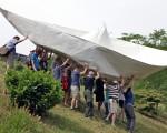 6月13日,德国艺术家驾驶9米长纸船航行,呼吁人们重视环境保护。图为大家帮忙将9米长的特大号纸船抬到河边(AFP PHOTO JAN WOITAS )