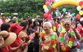 一对对老夫妻们携手步上红坛,在亲友的祝福下,整个会场洋溢着欢乐与幸福,大家抢著为老人家们拍下永恒的镜头。(摄影:廖素贞/大纪元)