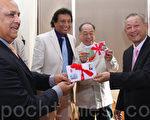模國郵政局局長(左二)和執行長(左一)頒發朱梅麟紀念郵票給朱梅麟長子朱長權(右二)、四子朱長淼(右一)(攝影: 戴德蔓 / 大紀元)