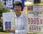 香港共有十多个退党点,每个点每天都能退几十人甚至上百人,一年退近10万人。图为旺角退党点义工阿媚,展示向游客派发的九评共产党等资料。(摄影:余钢/大纪元)