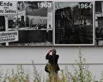 2011年8月13日,一名男子在伯瑙尔街的柏林墙上展示的历史图片前拍照。( MICHELE TANTUSSI / AFP ImageForum)