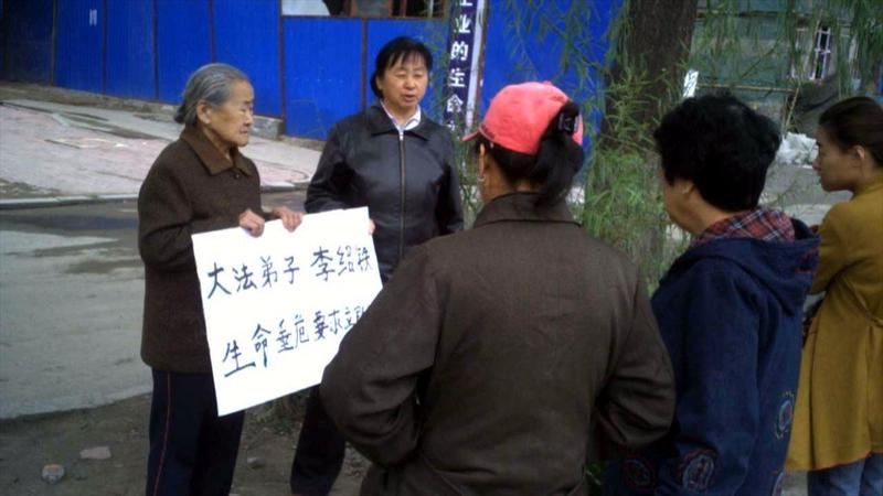 李紹鐵年近九旬的母親擧牌抗議,向中共要回自己的兒子。