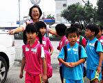 笑口常开的李丽华,每天在校门口快乐当导护志工,为学童的上学安全把关。(摄影:王镜瑜/大纪元)