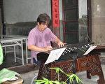 """陈信华在记者会现场演奏他的招牌曲""""沧海一声笑""""。(摄影:廖素贞/大纪元)"""