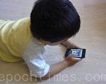 操作简单的智能手机让小孩子爱不释手(摄影:关宇宁/大纪元)
