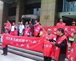 """上海讨房团身披""""还我经租房""""的红袍,手拉""""强烈要求撤销国家经租,还我私房!""""等横幅在上海市政大厦前,继续每周的讨房抗议示威。(知情者提供)"""